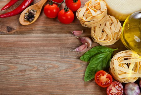 Italian cuisine. Vegetables, oil, spices and pasta on the table
