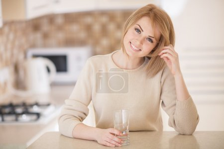 Beautiful woman in the kitchen with a glass of water
