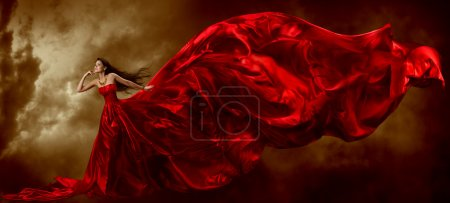 Woman in red waving beautiful dress with flying fabric, artistic sky