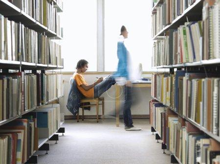 Boy doing homework in library