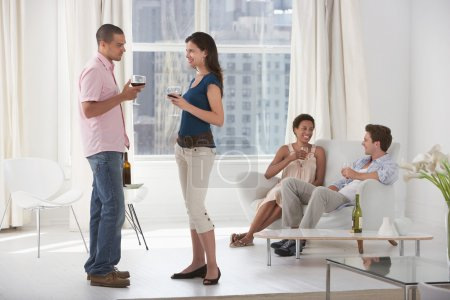 Couples drinking wine in living room