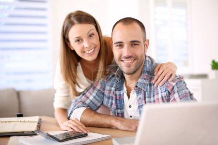 Smiling couple calculating savings
