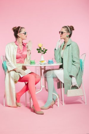 Two girls blonde hair fifties fashion style drinking tea.