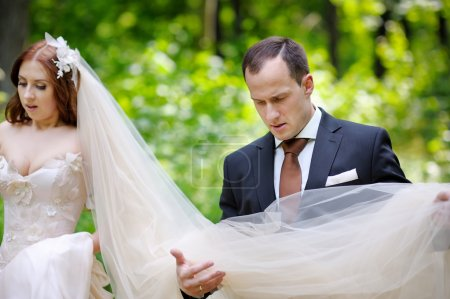 Young bride and groom in summer park