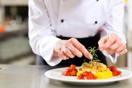 Female Chef in restaurant kitchen cooking