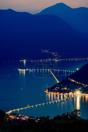 Sulzano, Italy - June 23, 2016: The floating piers. The artist Christo walkway on Lake Iseo, Montisola island. Last sun over Iseo Lake, nightlights.