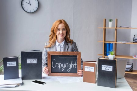Smiling lawyer showing chalkboard with copyright lettering near books, while sitting at workplace with documents