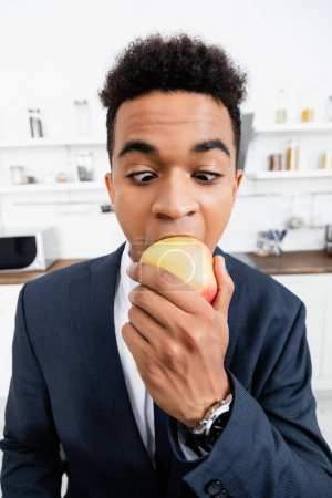 curly african american businessman eating fresh apple at home