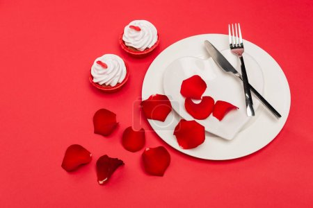 cupcakes near plate with rose petals and cutlery on red background