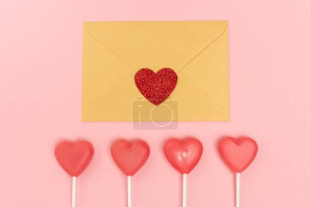 top view of heart shaped lollipops and envelope with heart on pink background