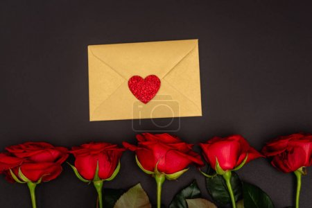 top view of roses and envelope isolated on black
