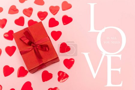 top view of red hearts and gift box near love is all you need lettering on pink background