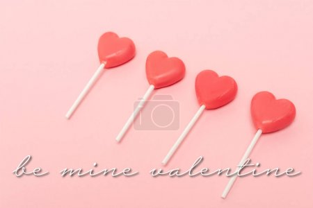 heart shaped lollipops near be mine valentine lettering on pink background