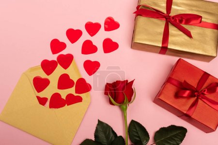 top view of red hearts, rose, envelope and gift boxes on pink background