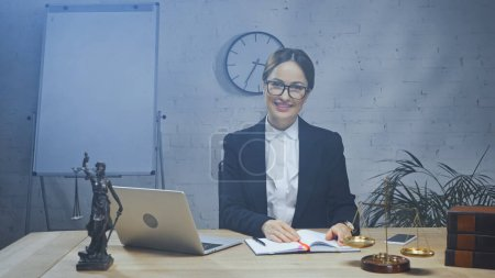 Smiling insurance agent looking at camera near devices, statuette of justice and scales in office