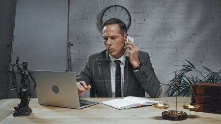 Insurance agent talking on smartphone near laptop, notebook and statuette of justice
