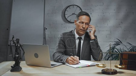 Insurance agent talking on smartphone near laptop, notebook and scales on table in office