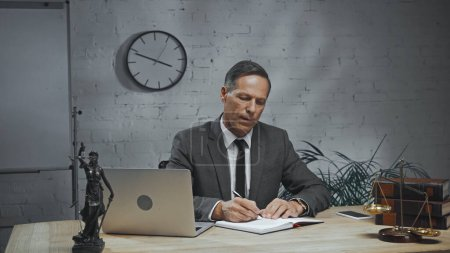 Insurance agent writing on notebook while working near devices and scales