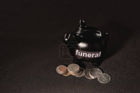 piggy bank with coins on black background, funeral concept