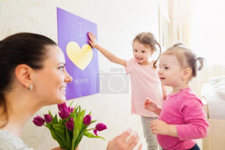Mothers day, girls giving flowers and card to their mum