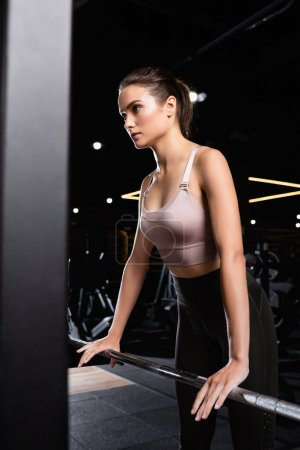 young sportswoman touching power rack in gym on blurred foreground