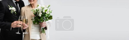 Cropped view of smiling bride toasting champagne with groom isolated on grey, banner