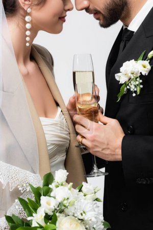 cropped view of elegant newlywed couple standing face to face and holding champagne glasses isolated on grey