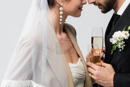 partial view of elegant bride and muslim man standing face to face with champagne glasses isolated on grey