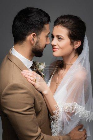 cheerful bride looking at arabian fiance isolated on grey