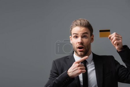 amazed businessman with open mouth pointing at credit card isolated on grey