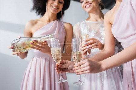 cropped view of african american woman pouring champagne into glasses of bride and bridesmaid, blurred background