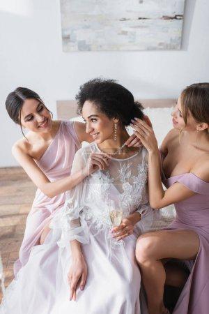 elegant bridesmaids preparing african american woman for wedding in bedroom