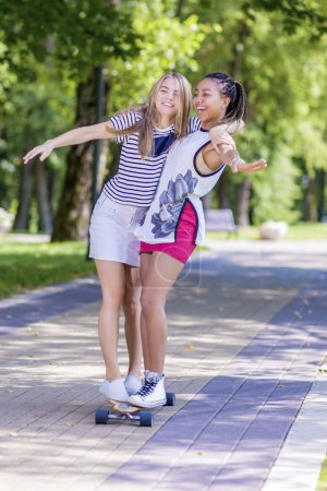 Two Happy Laughing Teenager Girls Skating Longboard Together in Park.