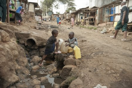 Boys take a water for drinking on a street of Kibera, Nairobi, Kenya.
