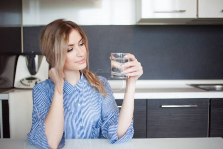 Attractive young woman drinking water in the kitchen. Habits for a healthy lifestyle