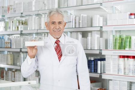 Pharmacist Holding Medicine Box Against Shelves