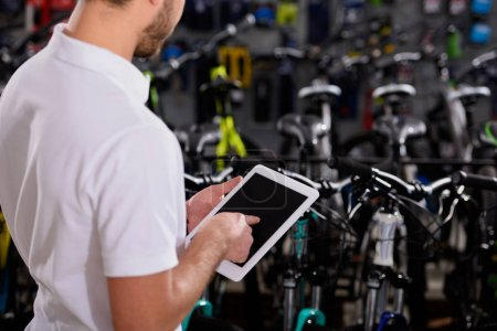 cropped shot of young man using digital tablet with blank screen in bicycle shop