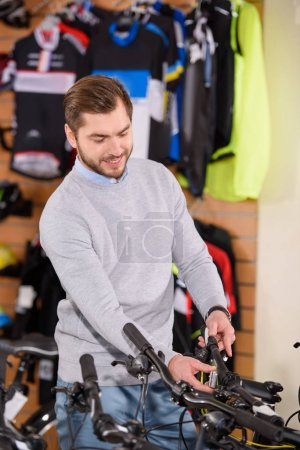 smiling young man looking at bikes in bicycle shop
