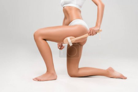 cropped view of slim woman in underwear massaging legs with wooden massage brush isolated on grey