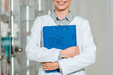 Cropped view of smiling pharmacist holding clipboard in drugstore
