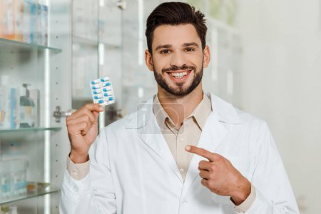 Handsome pharmacist smiling at camera and pointing at blister with pills