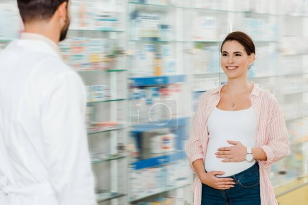 Selective focus of pregnant woman smiling to pharmacist with medicaments in showcase at background