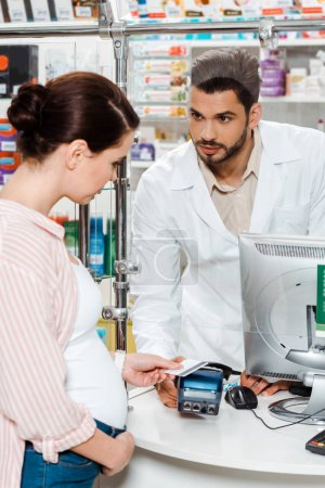Pharmacist looking at pregnant woman paying with paypass in drugstore