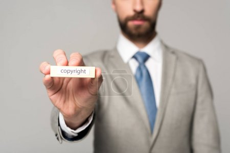 partial view of businessman showing wooden block with word copyright isolated on grey