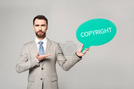 confident businessman pointing with hand at thought bubble with copyright inscription isolated on grey