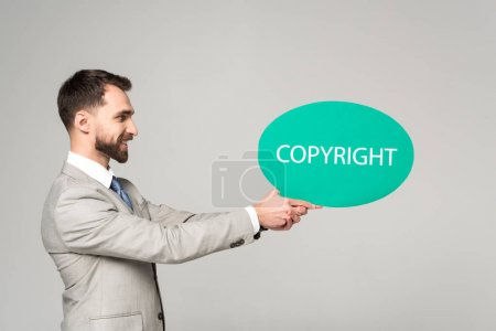 side view of smiling businessman holding thought bubble with copyright inscription isolated on grey