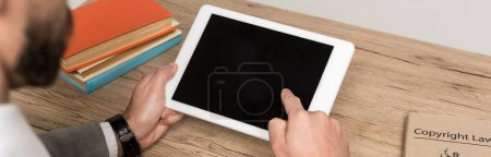cropped view of businessman holding digital tablet with blank screen isolated on grey, panoramic shot