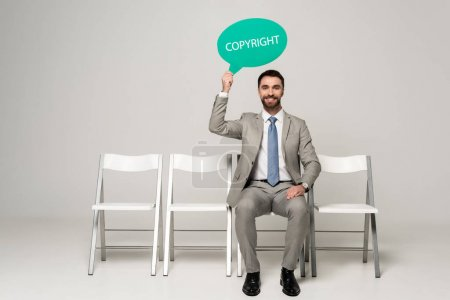cheerful businessman holding thought bubble with copyright inscription while sitting on chair on grey background