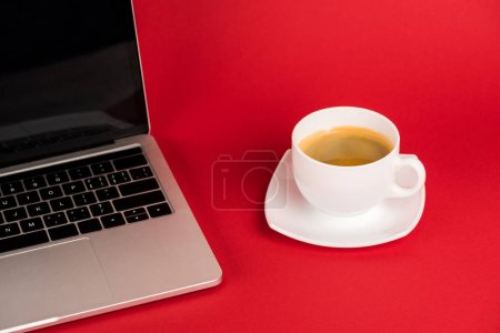 Laptop with blank screen and coffee cup on saucer on red background