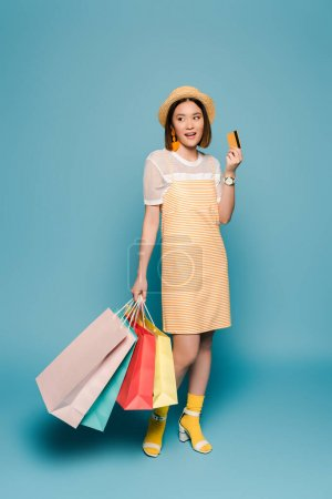 smiling asian girl in striped yellow dress and straw hat with shopping bags and credit card on blue background